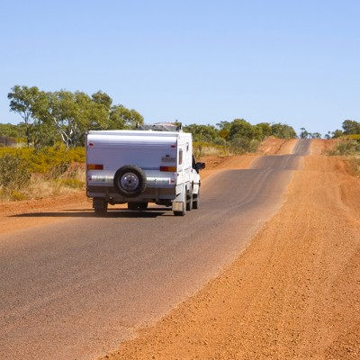 Back view of folding caravan being towed on a bumpy road in outback Queensland, Australia