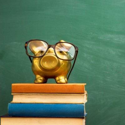 piggy bank with glasses on books, education concept